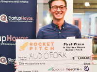 COURTESY JEFF REID  First place StartupHoyas Rocket Pitch winner Eric Wu (SFS '17) displays his $1,000 prize following the competition Tuesday evening. Wu pitched a mobile cooking application that provides hands-free guidance.