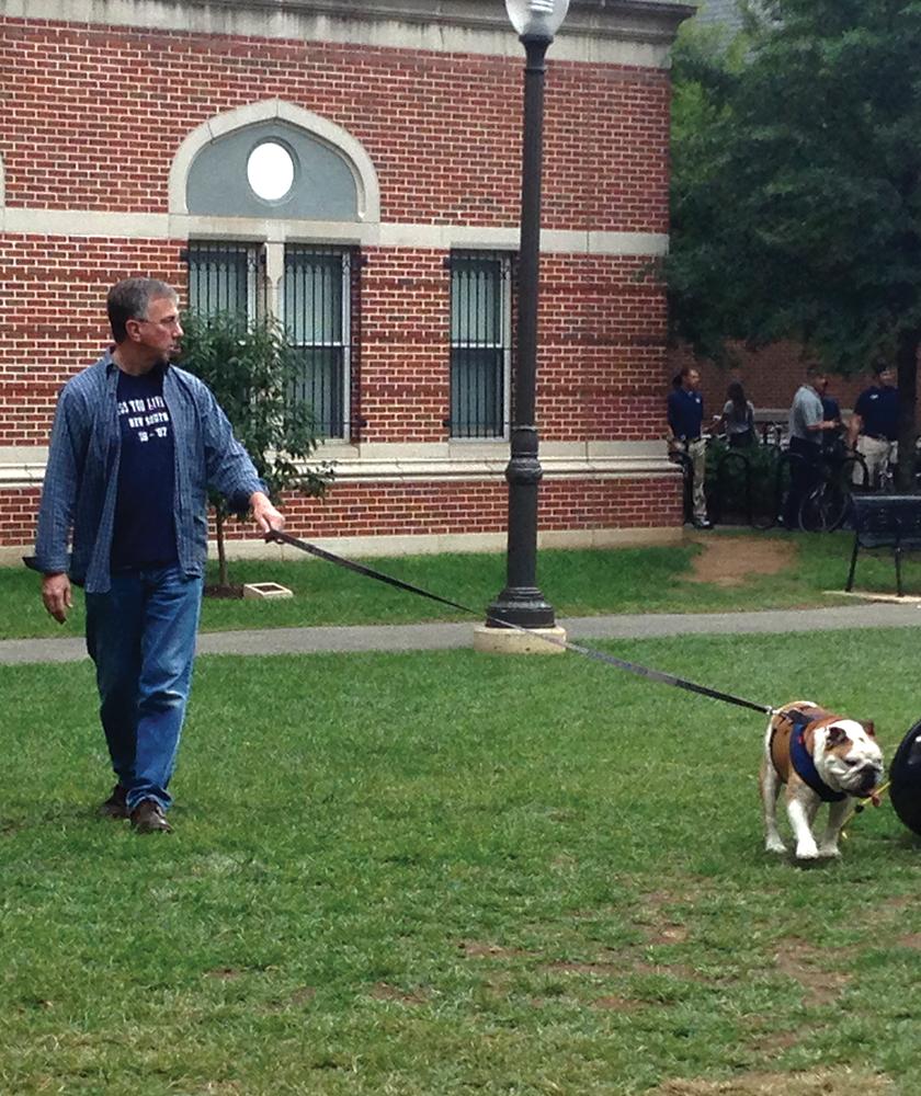 ALEXANDER BROWN/THE HOYA Fr. Christopher Steck, S.J., walks Jack the Bulldog. Steck will not be caretaker for the new mascot.