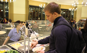 DANIEL SMITH/THE HOYA Phil Novacki (MSB '17), who is gluten-free, wrestles with acceptable food options while perusing stations on the top floor of O'Donovan Hall, which is seeking to become more gluten-free friendly.