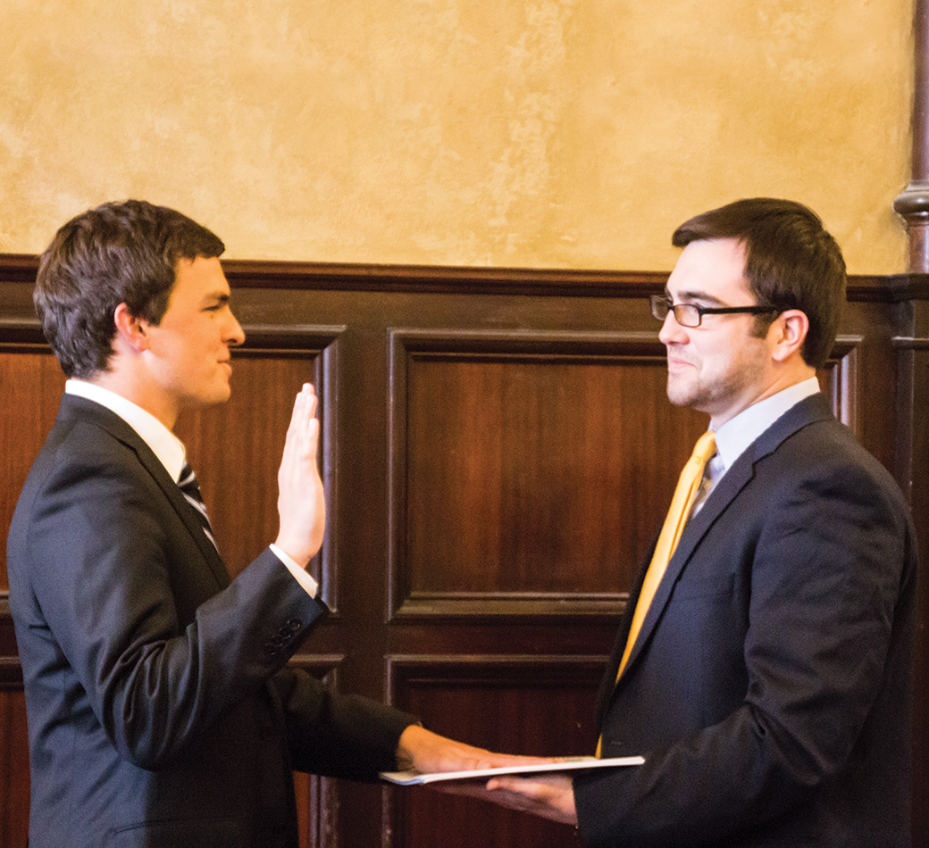 DANIEL SMITH/THE HOYA Trevor Tezel (SFS '15), left, takes the reins from outgoing GUSA  President Nate Tisa (SFS '14) in Healy Hall on Sunday.