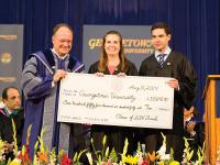 ALEXANDER BROWN/THE HOYA Senior Class Fund Co-Chairs Elizabeth Abello (COL '14) and Peter Brigham (SFS '14) present $155,640.40 to University President DeGioia.