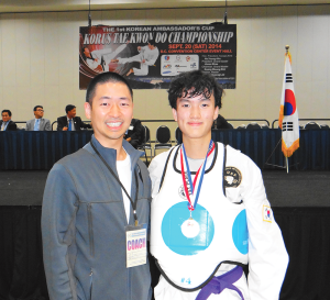 COURTESY OF GU TAE KNOW DO CLUB Sophomore Daniel Kim dons the gold medal alonside his coach and GU Tae Kwon Do Club Head Instructor, Master Mickey Lee (COL '05).