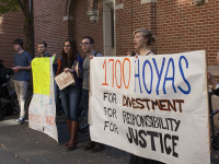 MICHELLE XU/THE HOYA Elaine Colligan (SFS '15) holds a banner advocating for divestment as a university committee discusses GU Fossil Free's proposal.