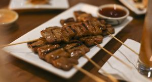 COURTESY CAMERON LANCASTER Spiced lime sauce coats grilled, skewered pork in the moo yang kati sod dish.