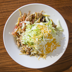 Choose chicken, beans, vegetables and guacamole for healthy fat in a tortilla-less burrito bowl. Limit the cheese and sour cream.