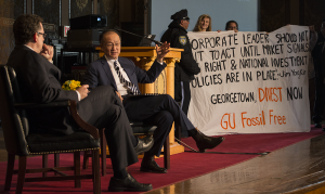 FILE PHOTO: NATE MOULTON/THE HOYA Members of GU Fossil Free hold a banner in Gaston Hall following a speech by World Bank President Jim Yong Kim. GUPD escorted them off the stage.