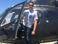 COURTESY MATTHEW ARONSON North by South founder Matthew Aronson (COL '15) steps out of a helicopter wearing one of his company's T-shirts with pockets made from necktie material. The startup now boasts more than 100 different designs.