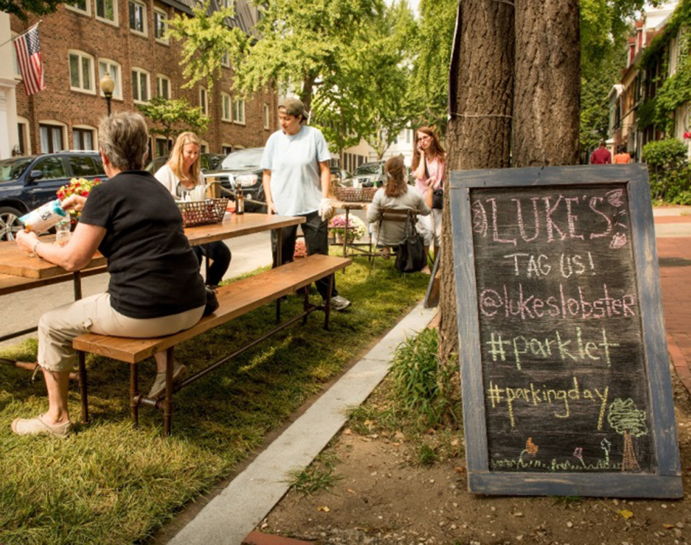 COURTESY GEORGETOWN BUSINESS IMPROVEMENT DISTRICT Customers enjoy food outside of Luke's Lobster at a parklet set up with tables for Park(ing) Day last year. The annual event returns to the district today with four parklets in Georgetown hosted by local businesses.