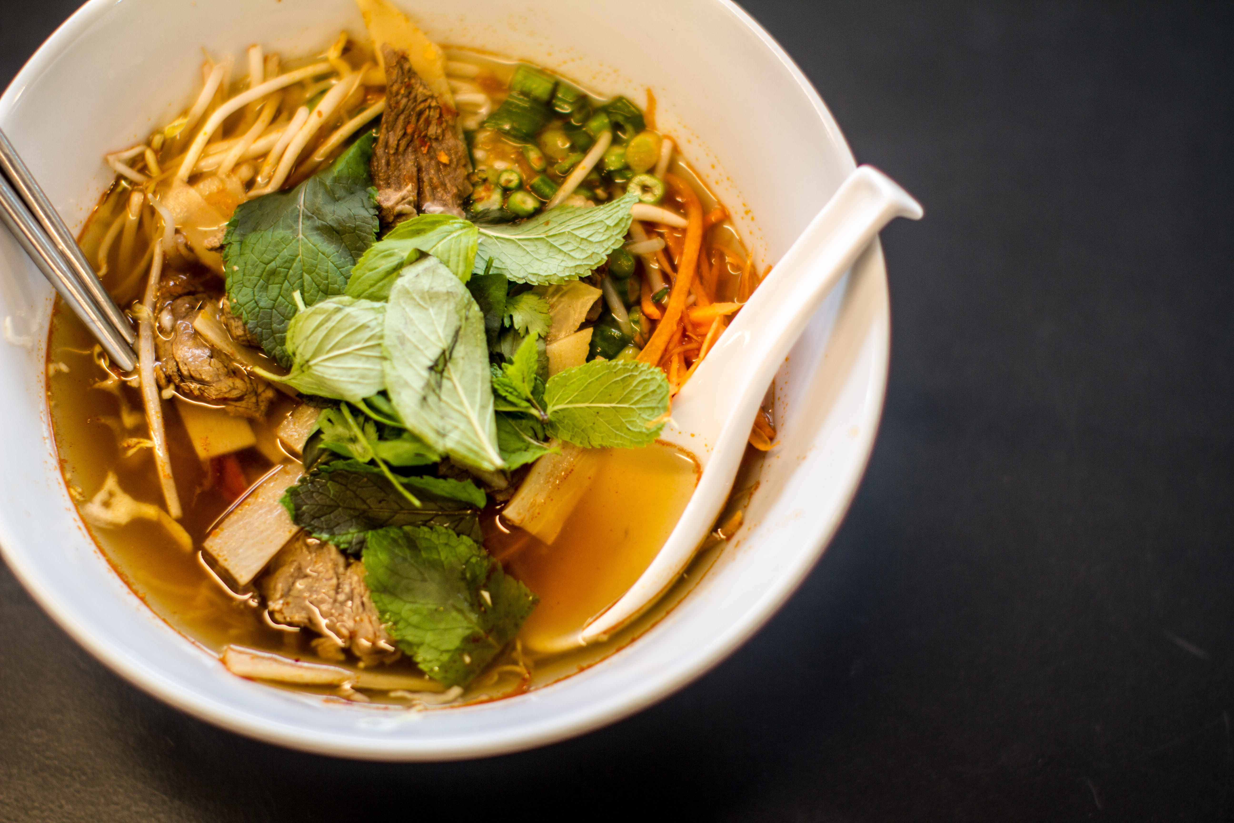 COURTESY FOODHINI Customers of Foodhini seek ethnic foods such as this Laotian soup, Khao Poon Nam Seen, a tomato-based broth with cuts of beef and bamboo, poured over rice noodles with mint and basil.