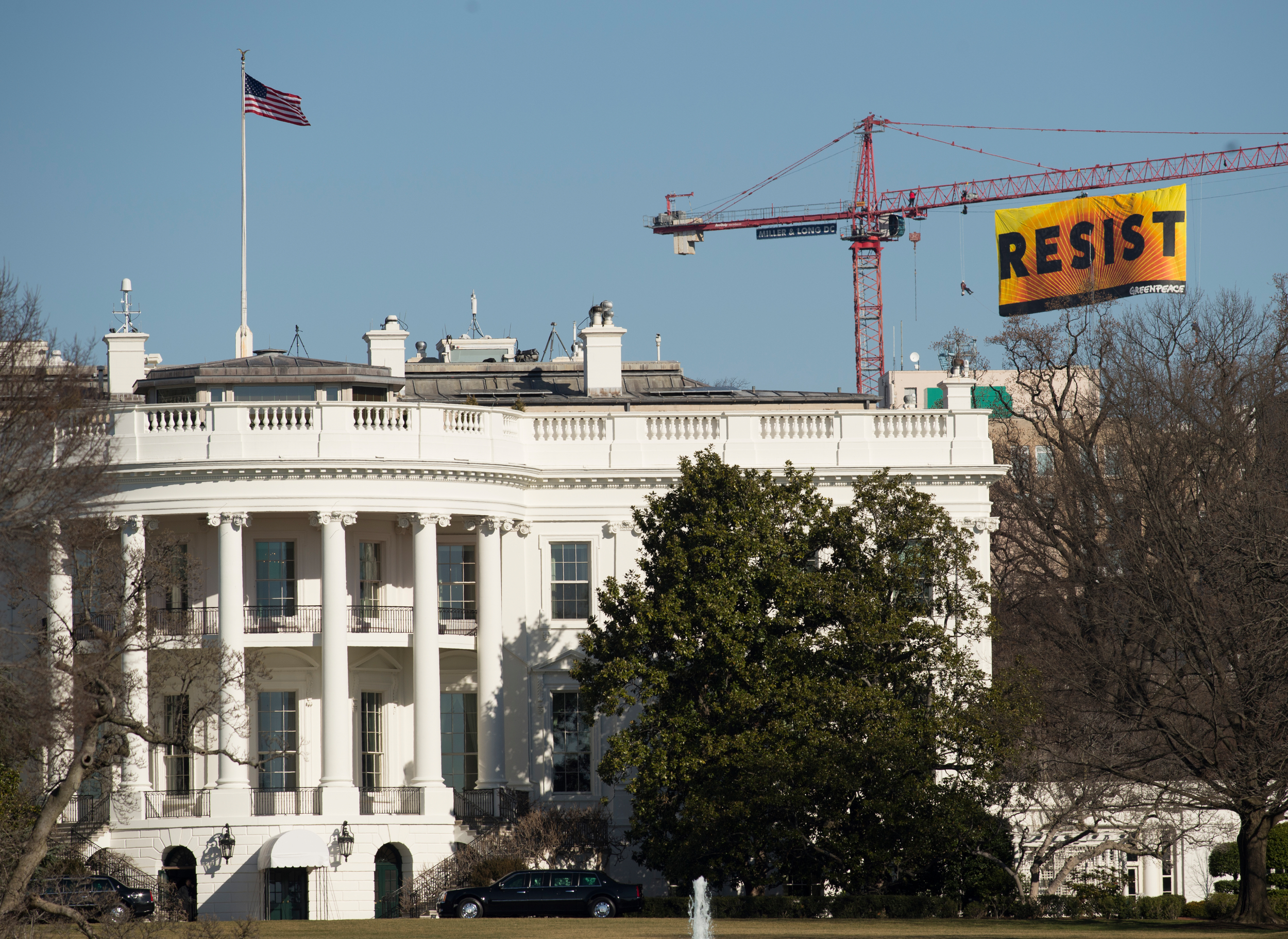 """PHOTO COURTESY GREENPEACE Seven Greenpeace activists were arrested last night around 10 p.m. for climbing a crane and hanging a banner with the word """"Resist"""" a few blocks from the White House to protest protest President Donald Trump's approval of the Keystone XL and Dakota Access pipelines, among other actions."""
