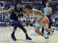KIRK ZIESER/THE HOYA | Freshman guard James Akinjo drives past Xavier sophomore guard Paul Scruggs.